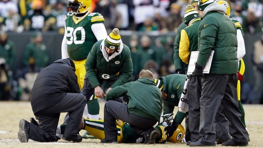 Jan. 5, 2014: Trainers check on Green Bay Packers cornerback Sam Shields (37) during the first half of an NFL wild-card playoff football game against the San Francisco 49ers in Green Bay, Wis.