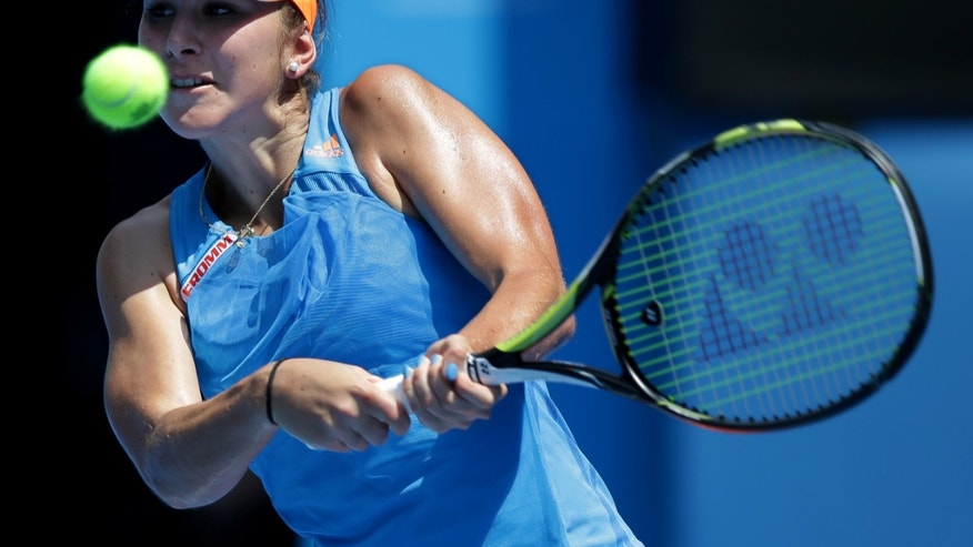 Belinda Bencic of Switzerland makes a backhand return to Li Na of China during their second round match at the Australian Open tennis championship in Melbourne, Australia, Wednesday, Jan. 15, 2014.(AP Photo/Aaron Favila)