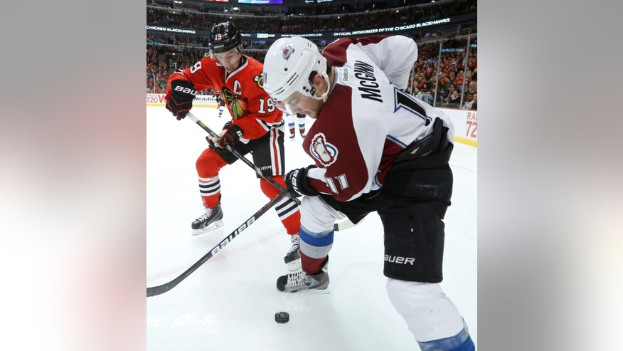 Chicago Blackhawks center Jonathan Toews (19) and Colorado Avalanche left wing Jamie McGinn battle for a loose puck along the boards during the second period of an NHL hockey game, Tuesday, Jan. 14, 2014, in Chicago. (AP Photo/Charles Rex Arbogast)