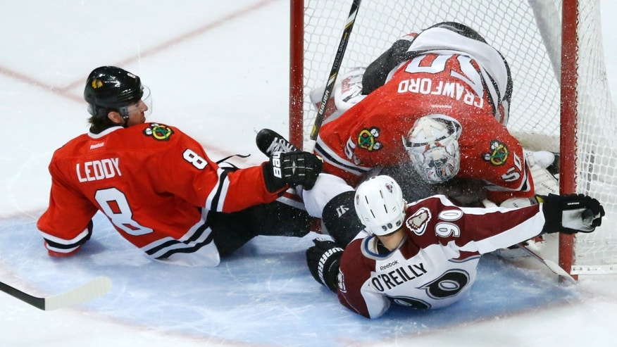 Chicago Blackhawks defenseman Nick Leddy (8) and Colorado Avalanche center Ryan O'Reilly slide into goalie Corey Crawford and the net during the first period of an NHL hockey game, Tuesday, Jan. 14, 2014, in Chicago. (AP Photo/Charles Rex Arbogast)