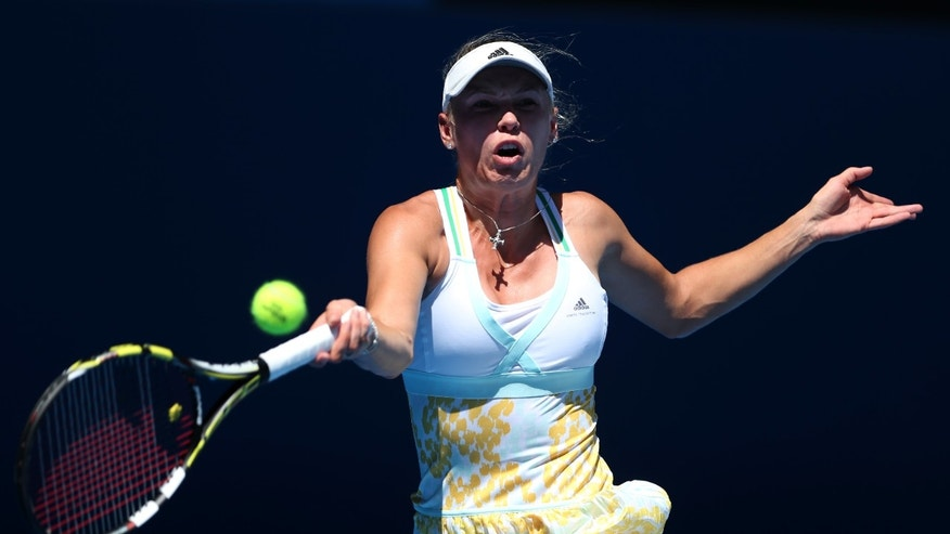 Caroline Wozniacki of Denmark makes a forehand return to  Lourdes Dominguez Lino of Spain during their first round match at the Australian Open tennis championship in Melbourne, Australia, Tuesday, Jan. 14, 2014.(AP Photo/Rick Rycroft)
