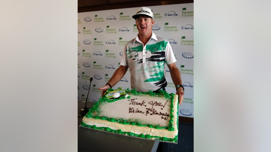 Brian Gay, last year's Humana Challenge golf tournament winner, poses with a cake he presented to members of the media before a news conference at the tournament at PGA West on Wednesday, Jan. 15, 2014, in La Quinta, Calif. (AP Photo/Chris Carlson)