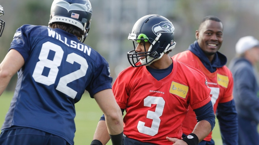 Seattle Seahawks quarterback Russell Wilson (3) greets tight end Luke Willson (82) at the start of NFL football practice on Wednesday, Jan. 15, 2014, in Renton, Wash. The Seahawks are to play the San Francisco 49ers on Sunday in the NFC championship. (AP Photo/Ted S. Warren)