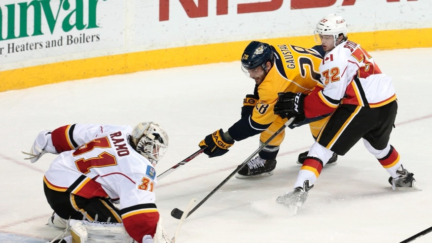 Calgary Flames goalie Karri Ramo (31), of Finland, blocks a shot as Paul Byron (32) keeps Nashville Predators forward Paul Gaustad (28) away from the goal in the second period of an NHL hockey game Tuesday, Jan. 14, 2014, in Nashville, Tenn. (AP Photo/Mark Humphrey)