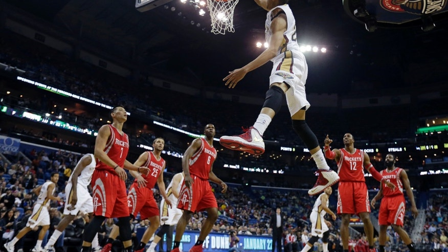 New Orleans Pelicans power forward Anthony Davis (23) slam dunks in the first half of an NBA basketball game against the Houston Rockets in New Orleans, Wednesday, Jan. 15, 2014. (AP Photo/Gerald Herbert)