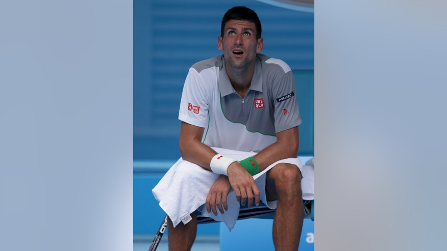 Novak Djokovic of Serbia waits in his seat during break in his second round match against Leonardo Mayer of Argentina at the Australian Open tennis championship in Melbourne, Australia, Wednesday, Jan. 15, 2014.(AP Photo/Aaron Favila)