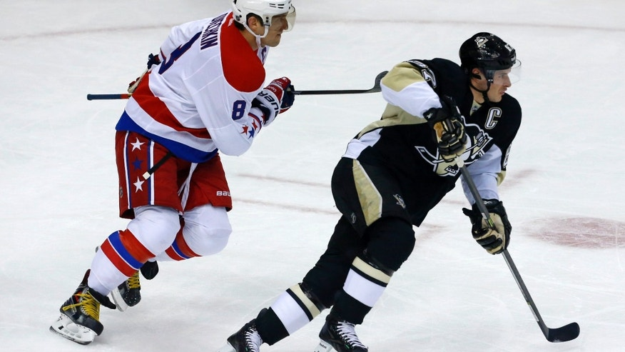 Pittsburgh Penguins' Sidney Crosby (87) and Washington Capitals' Alex Ovechkin (8) skate during the first period of an NHL hockey game in Pittsburgh, Wednesday, Jan. 15, 2014. (AP Photo/Gene J. Puskar)