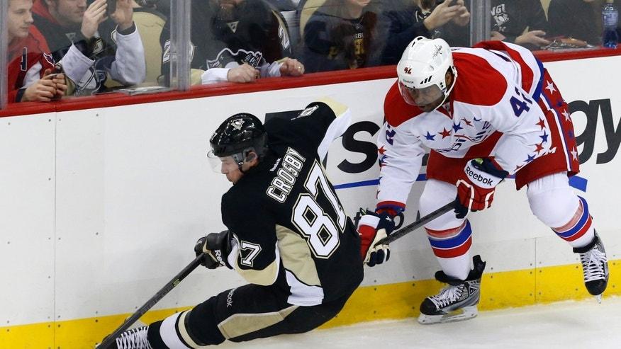 Washington Capitals' Joel Ward (42) trips Pittsburgh Penguins' Sidney Crosby (87) during the first period of an NHL hockey game in Pittsburgh, Wednesday, Jan. 15, 2014. (AP Photo/Gene J. Puskar)