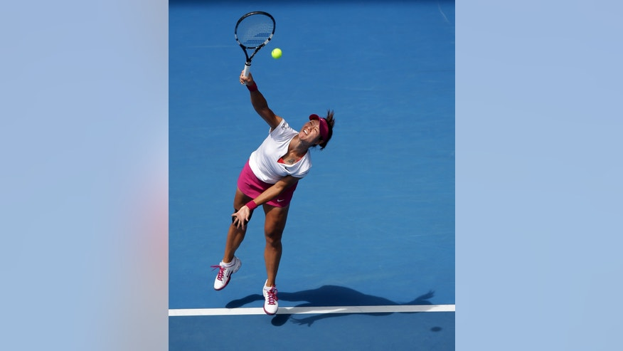 Li Na of China serves to Belinda Bencic of Switzerland during their second round match at the Australian Open tennis championship in Melbourne, Australia, Wednesday, Jan. 15, 2014.(AP Photo/Aaron Favila)