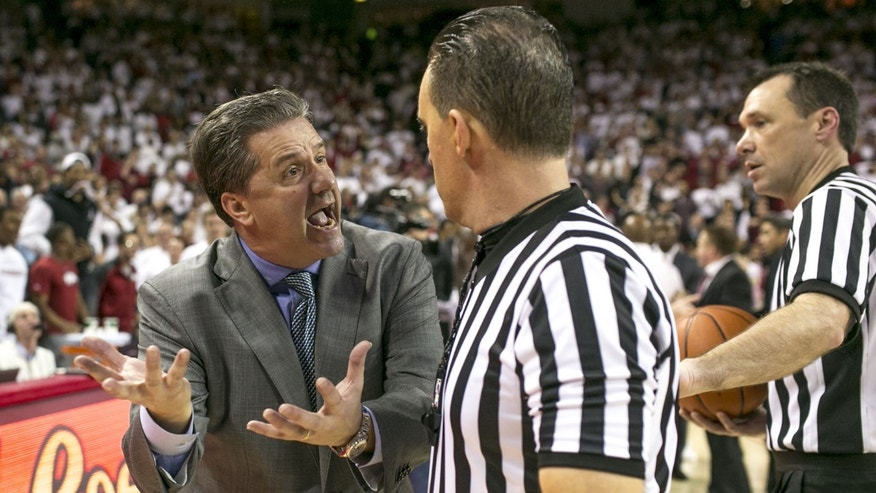 Kentucky head coach John Calipari complains to a referee after an overtime loss in an NCAA college basketball game against Arkansas on Tuesday, Jan. 14, 2014, in Fayetteville, Ark. (AP Photo/Gareth Patterson)