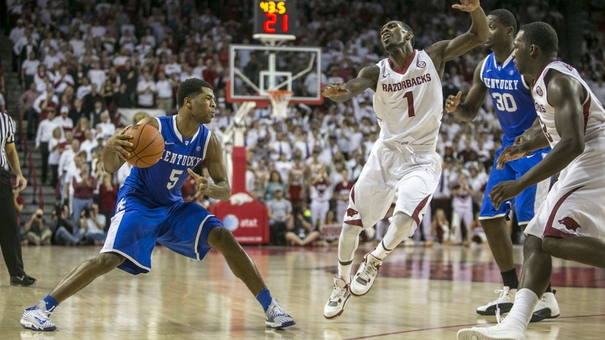 Kentucky guard Andrew Harrison, (5), recovers from a faked shot as Arkansas guard Mardracus Wade, (1), attempts a block during the second half of an NCAA college basketball game on Tuesday, Jan. 14, 2014, in Fayetteville, Ark. (AP Photo/Gareth Patterson)