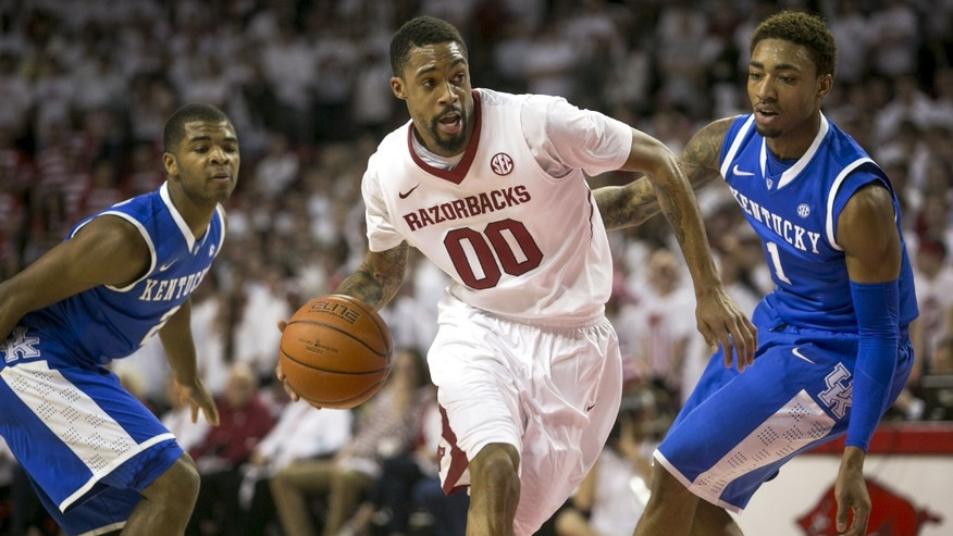 Arkansas guard Rashad Madden (00) drives to the basket against Kentucky guards Aaron Harrison (2) and James Young (1) during the first half of an NCAA college basketball game, Tuesday, Jan. 14, 2014, in Fayetteville, Ark. (AP Photo/Gareth Patterson)