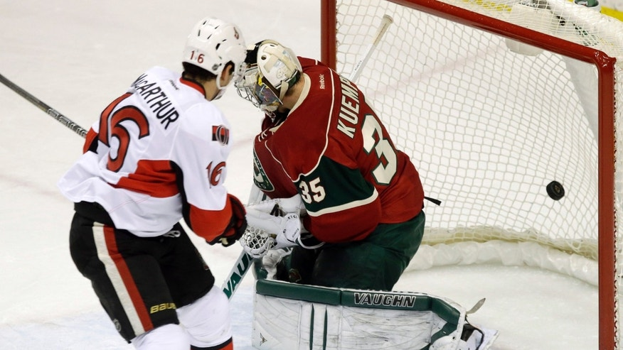Ottawa Senators' Clarke MacArthur, left, scores a power play goal against Minnesota Wild goalie Darcy Kuemper in the first period of an NHL hockey game, Tuesday, Jan. 14, 2014, in St. Paul, Minn. (AP Photo/Jim Mone)