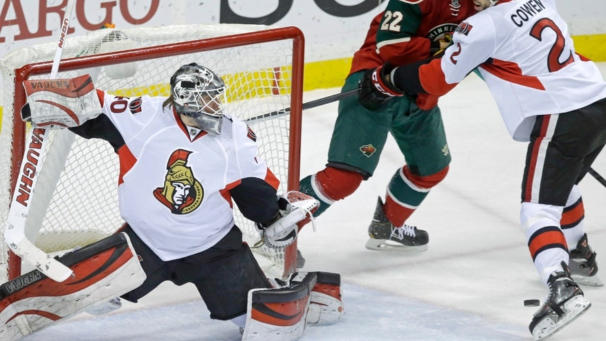 Ottawa Senators goalie Robin Lehner, left, of Sweden, defends as teammate Jared Cowen, right, keeps Minnesota Wild's Nino Niederreiter, center, of Switzerland at bay in the first period of an NHL hockey game, Tuesday, Jan. 14, 2014 in St. Paul, Minn. (AP Photo/Jim Mone)