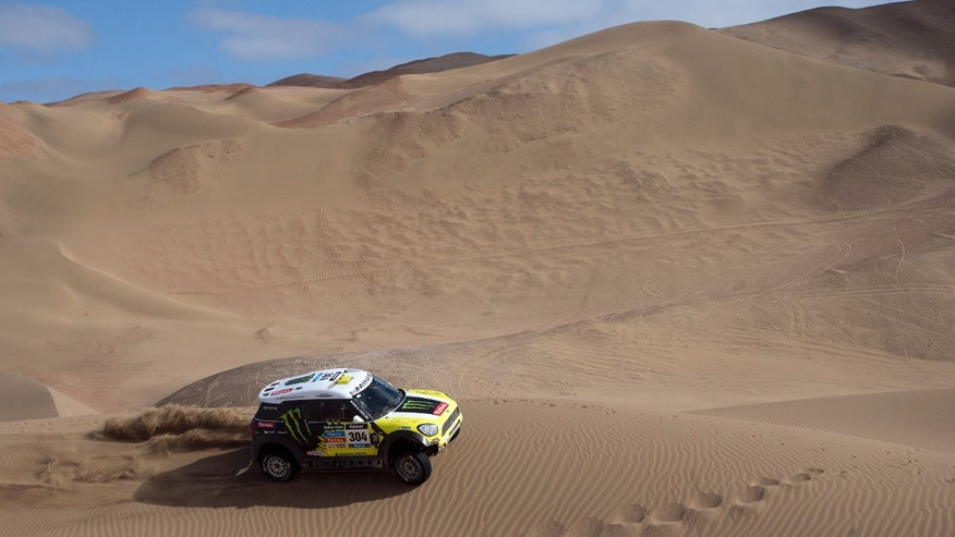 "Joan ""Nani"" Roma, of Spain, and co-pilot Michel Perin, of France, drive their Mini through the dunes during the tenth stage of the Dakar Rally between the cities of Iquique and Antofagasta, Chile, Wednesday, Jan. 15, 2014. (AP Photo/Victor R. Caivano)"