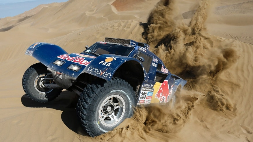 Carlos Sainz of Spain and co-pilot Timo Gottschalk of Germany drive their buggy through the dunes during the tenth stage of the Dakar Rally between the cities of Iquique and Antofagasta, Chile, Wednesday, Jan. 15, 2014. (AP Photo/Victor R. Caivano)