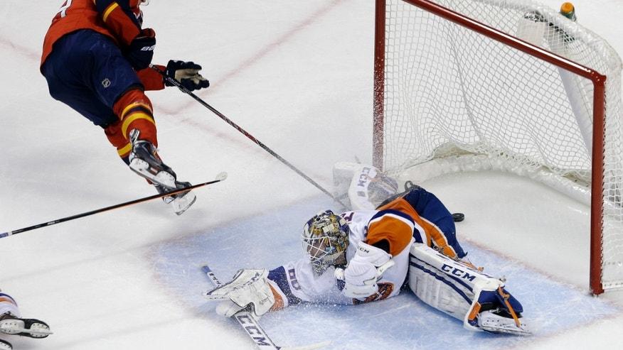 Florida Panthers' Scottie Upshall (19) scores a goal against New York Islanders goalie Kevin Poulin during the second period of an NHL hockey game, Tuesday, Jan. 14, 2014, in Sunrise, Fla. (AP Photo/Lynne Sladky)