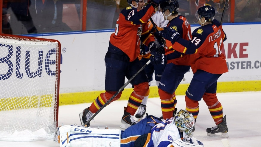 Florida Panthers' Nick Bjugstad, left, celebrates with Scottie Upshall, center, and Tomas Fleischmann (14) after scoring a goal against New York Islanders goalie Kevin Poulin, foreground, during the first period of an NHL hockey game, Tuesday, Jan. 14, 2014, in Sunrise, Fla. (AP Photo/Lynne Sladky)