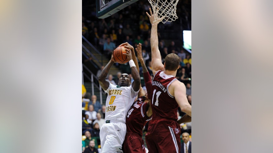 George Mason's Bryon Allen (0) goes to the basket against Massachusetts forward Raphiael Putney, center, and Tyler Bergantino (11) during the second half of an NCAA college basketball game, Wednesday, Jan. 15, 2014, in Fairfax, Va. Massachusetts won 88-87. (AP Photo/Nick Wass)