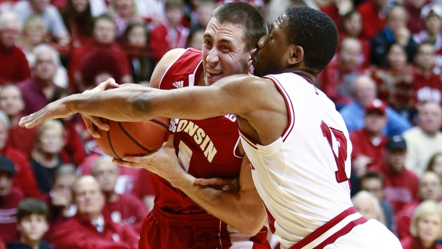 Wisconsin guard Josh Gasser, left, keeps the basketball away from Indiana guard Evan Gordon in the first half of an NCAA basketball game in Bloomington, Ind., Tuesday, Jan. 14, 2014. (AP Photo/R Brent Smith)