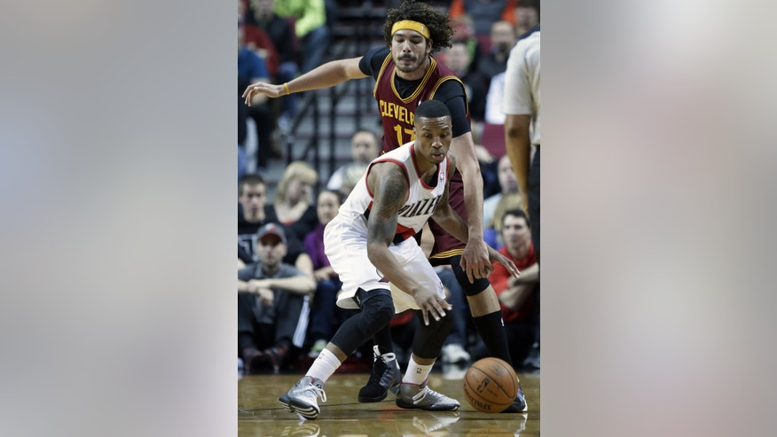 Portland Trails Blazers guard Damian Lillard, front, looks for room to maneuver as Cleveland Cavaliers center Anderson Varejao, from Brazil, defends during the first half of an NBA basketball game in Portland, Ore., Wednesday, Jan. 15, 2014. (AP Photo/Don Ryan)