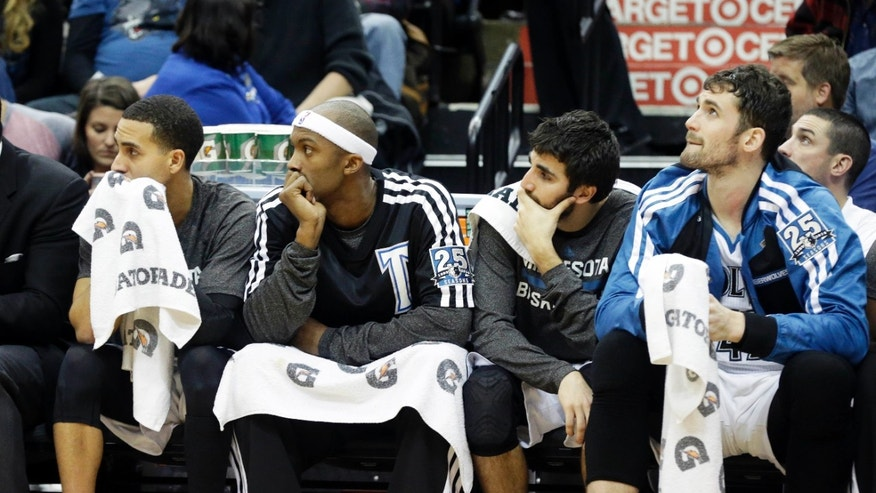 Minnesota Timberwolves, from left, Derrick Martin, Dante Cunningham, Ricky Rubio of Spain and Kevin Love watch from the bench in the second half of an NBA basketball game against the Sacramento Kings, Wednesday, Jan. 15, 2014, in Minneapolis. The Kings won 111-108. Love led the Timberwolves with 27 points and 11 rebounds. (AP Photo/Jim Mone)