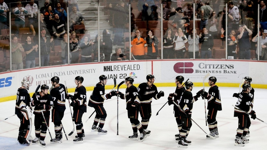 The Anaheim Ducks players celebrate their 9-1 win against the Vancouver Canucks after an NHL hockey game on Wednesday, Jan. 15, 2014, in Anaheim, Calif. (AP Photo/Jae C. Hong)