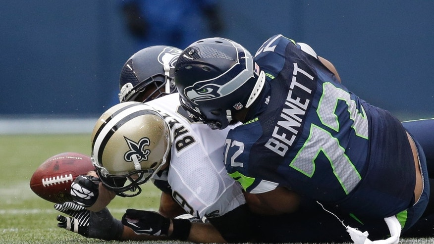 New Orleans Saints quarterback Drew Brees, left, fumbles the ball as he is sacked by Seattle Seahawks defensive end Cliff Avril, hidden, and defensive end Michael Bennett (72) during the third quarter of an NFC divisional playoff NFL football game in Seattle, Saturday, Jan. 11, 2014. The Saints recovered the fumble. (AP Photo/Elaine Thompson)