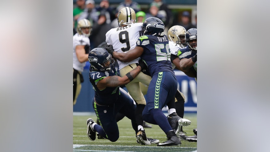 Seattle Seahawks defensive end Michael Bennett (72) and defensive end Cliff Avril (56) sack New Orleans Saints quarterback Drew Brees (9) during the third quarter of an NFC divisional playoff NFL football game in Seattle, Saturday, Jan. 11, 2014. (AP Photo/Elaine Thompson)