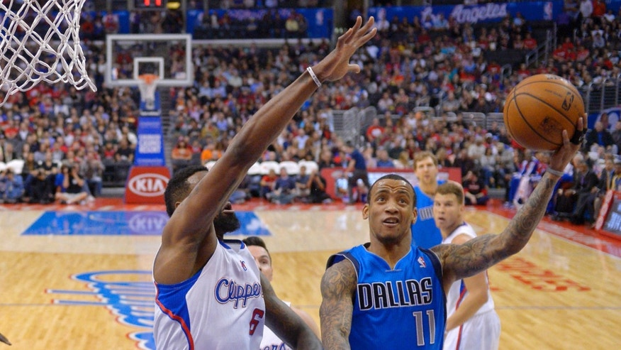 Dallas Mavericks guard Monta Ellis, right, puts up a shot as Los Angeles Clippers center DeAndre Jordan defends during the first half of an NBA basketball game, Wednesday, Jan. 15, 2014, in Los Angeles. (AP Photo/Mark J. Terrill)