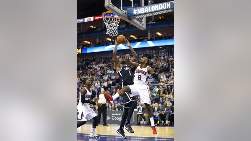 Atlanta Hawks' Shelvin Mack, right, tries to block a shot by Brooklyn Nets' Andray Blatche during an NBA basketball game at the O2 Arena in London, Thursday, Jan. 16, 2014. (AP Photo/Kirsty Wigglesworth)