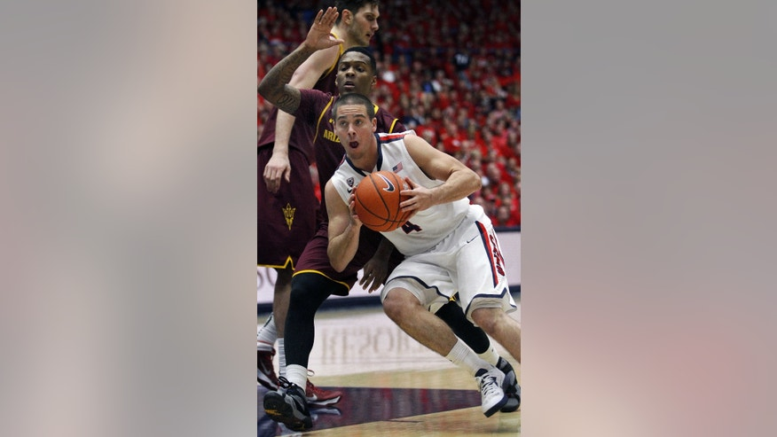 Arizona's T.J. McConnell (4) drives past Arizona State's Jahil Carson in the first half of an NCAA college basketball game on Thursday, Jan. 16, 2014, in Tucson, Ariz. (AP Photo/John Miller)