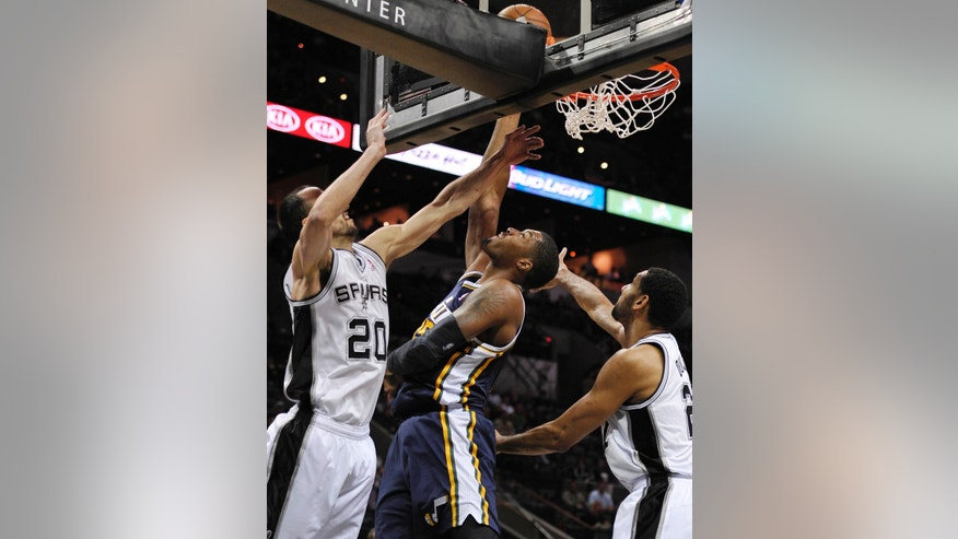Utah Jazz forward Derrick Favors, center, shoots against San Antonio Spurs guard Manu Ginobili, left, of Argentina, and forward Tim Duncan during the first half of an NBA basketball game, Wednesday, Jan. 15, 2014, in San Antonio. (AP Photo/Darren Abate)