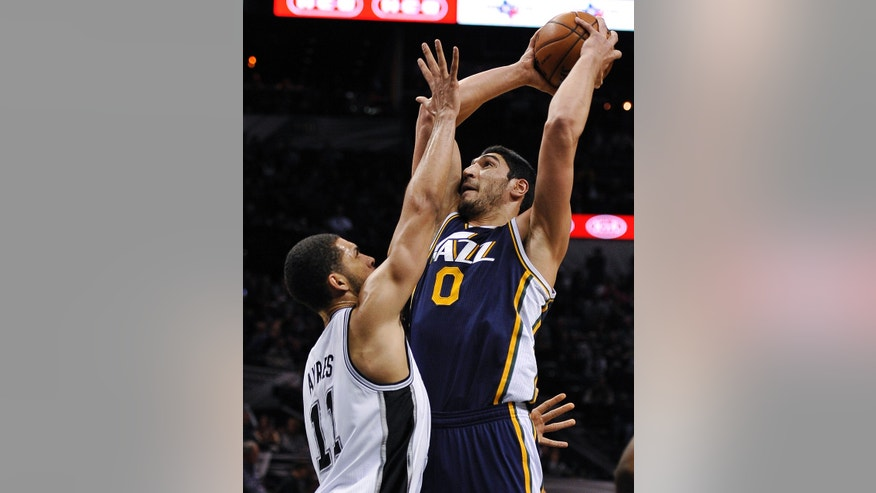 Utah Jazz center Enes Kanter shoots over San Antonio Spurs forward Jeff Ayres during the first half of an NBA basketball game, Wednesday, Jan. 15, 2014, in San Antonio. (AP Photo/Darren Abate)