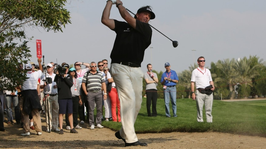 Phil Mickelson of the U.S. follows his ball on the 2nd hole during the 1st round of the Abu Dhabi HSBC Golf Championship in Abu Dhabi, United Arab Emirates, Thursday, Jan. 16, 2014. (AP Photo/Kamran Jebreili)