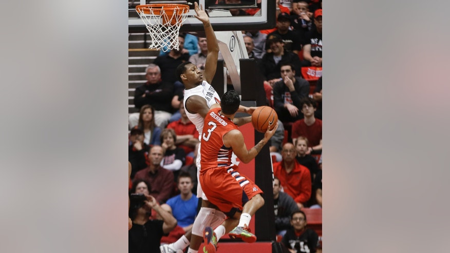 Fresno State guard Cezar Guerrero is turned away by the defense of San Diego State center Skylar Spencer during the first half of an NCAA college basketball game Wednesday, Jan. 15, 2014, in San Diego. (AP Photo/Lenny Ignelzi)