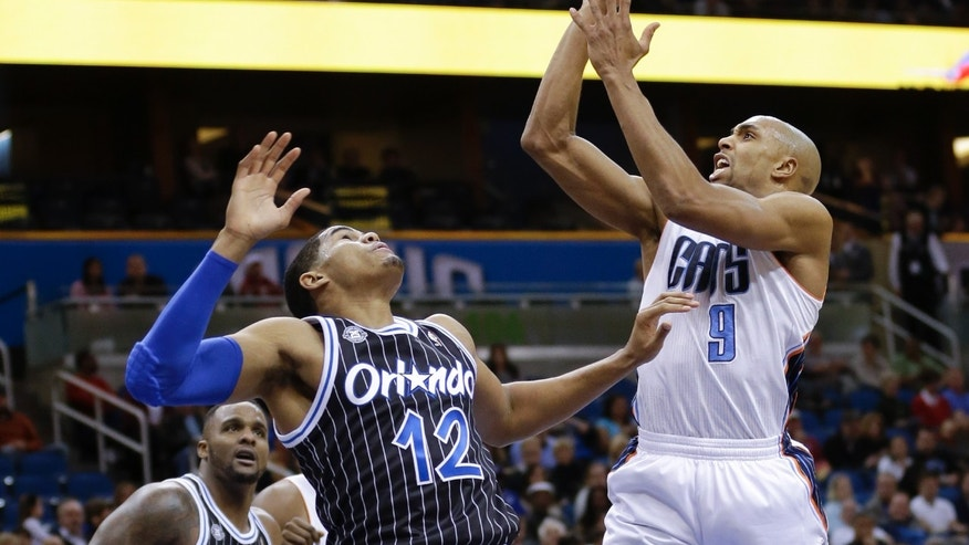 Charlotte Bobcats' Gerald Henderson (9) takes a shot over Orlando Magic's Tobias Harris (12) during the first half of an NBA basketball game in Orlando, Fla., Friday, Jan. 17, 2014. (AP Photo/John Raoux)