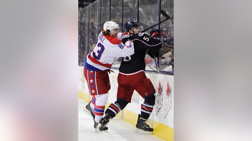 Washington Capitals' Jay Beagle, left, checks Columbus Blue Jackets' David Savard during the first period of an NHL hockey game on Friday, Jan. 17, 2014, in Columbus, Ohio. (AP Photo/Jay LaPrete)
