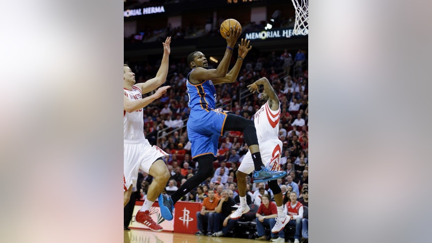 Oklahoma City Thunder's Kevin Durant, center, goes up for a shot as Houston Rockets' Aaron Brooks (0) and Donatas Motiejunas (20) defend during the first quarter of an NBA basketball game, Thursday, Jan. 16, 2014, in Houston. Durant was fouled by Brooks on the play. (AP Photo/David J. Phillip)