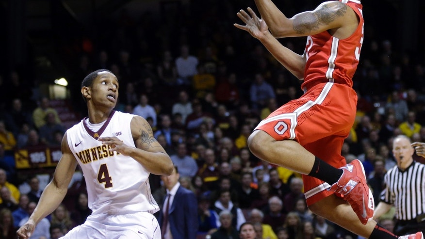 Ohio State's Lenzelle Smith Jr., right, lays up as Minnesota's Deandre Mathieu looks on in the first half of an NCAA college basketball game, Thursday, Jan. 16, 2014, in Minneapolis. (AP Photo/Jim Mone)