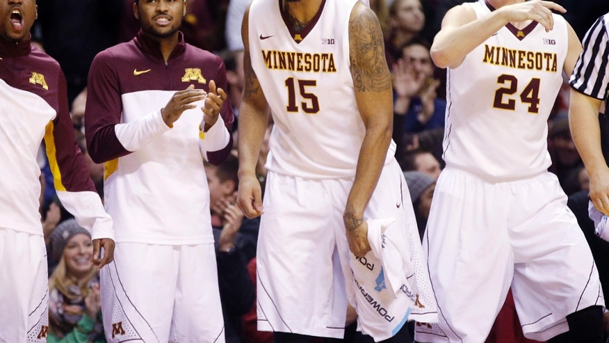 Minnesota's Maurice Walker (15), Joey King (24) and others celebrate a basket late in the second half of an NCAA college basketball game against Ohio State, Thursday, Jan. 16, 2014, in Minneapolis. Minnesota won 63-53. (AP Photo/Jim Mone)