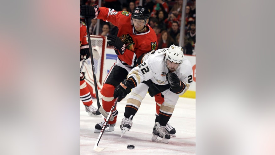 Anaheim Ducks' Mathieu Perreault (22) controls the puck against Chicago Blackhawks' Michal Handzus (26) during the first period of an NHL hockey game in Chicago, Friday, Jan. 17, 2014. (AP Photo/Nam Y. Huh)