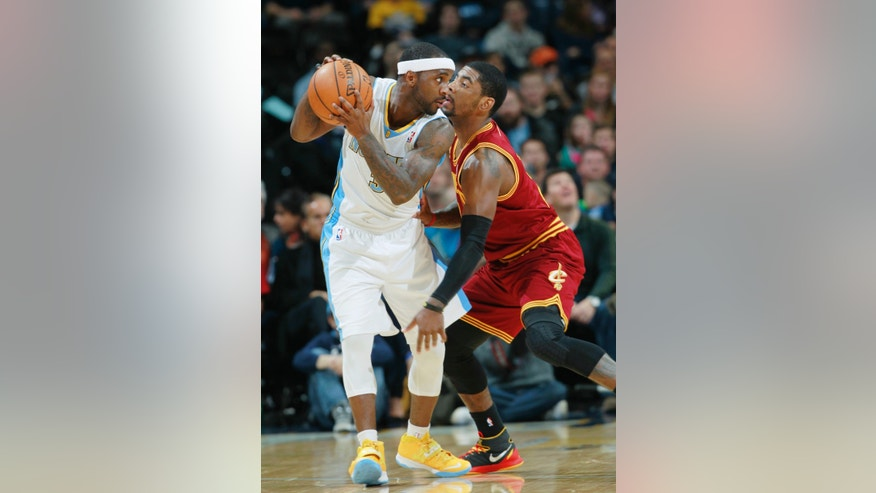 Denver Nuggets guard Ty Lawson, left, looks to pass ball as Cleveland Cavaliers guard Kyrie Irving covers in the first quarter of an NBA basketball game in Denver on Friday, Jan. 17, 2014. (AP Photo/David Zalubowski)
