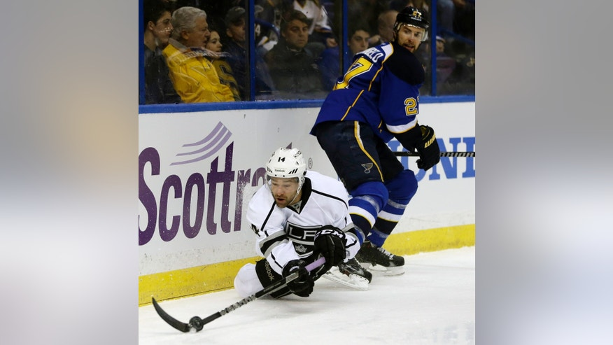 Los Angeles Kings' Justin Williams, bottom, passes the puck as he falls while St. Louis Blues' Alex Pietrangelo watches during the first period of an NHL hockey game, Thursday, Jan. 16, 2014, in St. Louis. (AP Photo/Jeff Roberson)