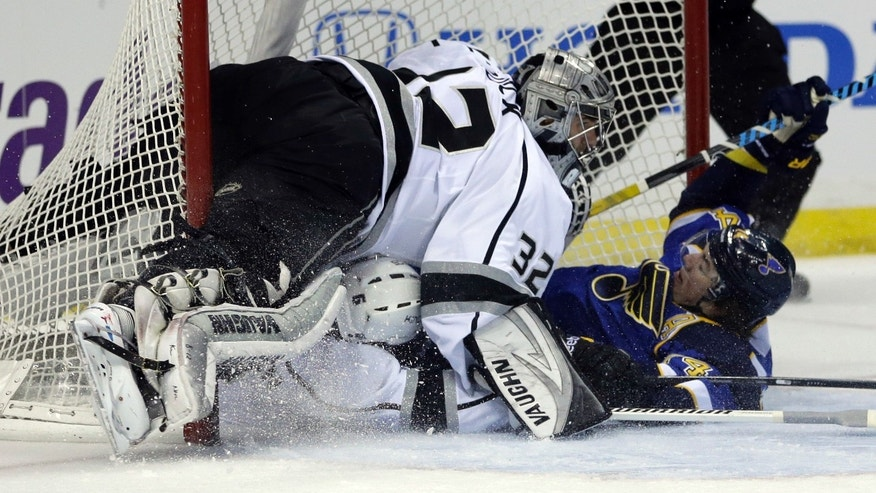 St. Louis Blues' T.J. Oshie, right, slides into the goal past Los Angeles Kings goalie Jonathan Quick, top left, after being taken down by Kings' Jake Muzzin during the second period of an NHL hockey game, Thursday, Jan. 16, 2014, in St. Louis. Oshie was awarded a penalty shot and scored following the play. (AP Photo/Jeff Roberson)
