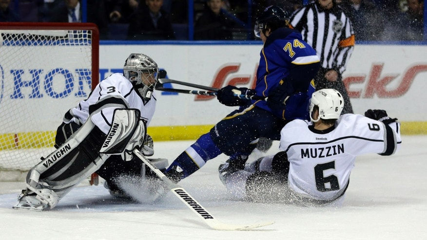St. Louis Blues' T.J. Oshie (74) is taken down from behind by Los Angeles Kings' Jake Muzzin (6) as Kings goalie Jonathan Quick watches during the second period of an NHL hockey game, Thursday, Jan. 16, 2014, in St. Louis. Oshie was awarded a penalty shot and scored following the play. (AP Photo/Jeff Roberson)