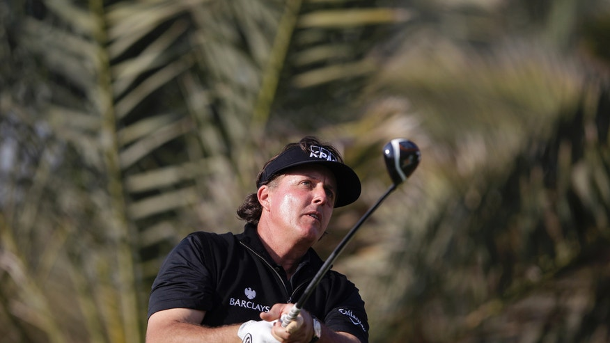 Phil Mickelson of the U.S. follows his ball on the 14th hole during the 2nd round of the Abu Dhabi HSBC Golf Championship in Abu Dhabi, United Arab Emirates, Friday Jan. 17, 2014. (AP Photo/Kamran Jebreili)