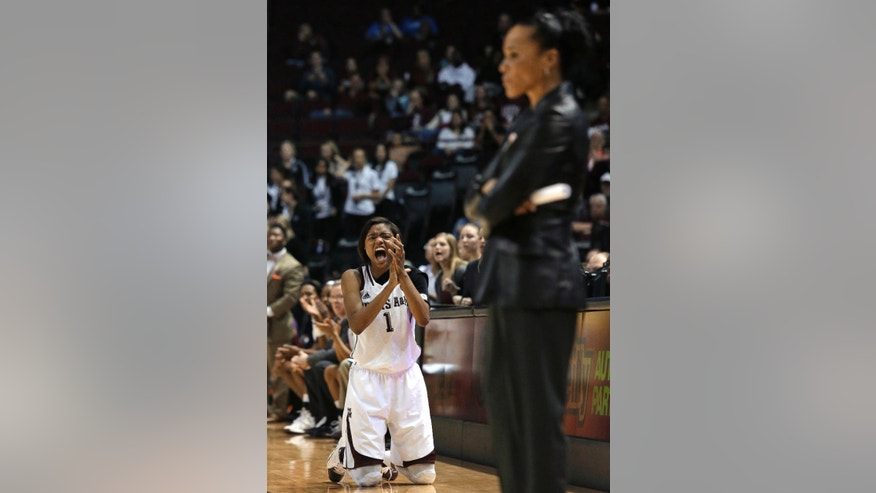 Texas A&M guard Courtney Williams (1) celebrates a score while South Carolina coach Dawn Staley stands in the foreground during the second half of an NCAA college basketball game, Thursday, Jan. 16, 2014, in College Station, Texas. Texas A&M defeated South Carolina 67-65 in overtime.  (AP Photo/Patric Schneider)