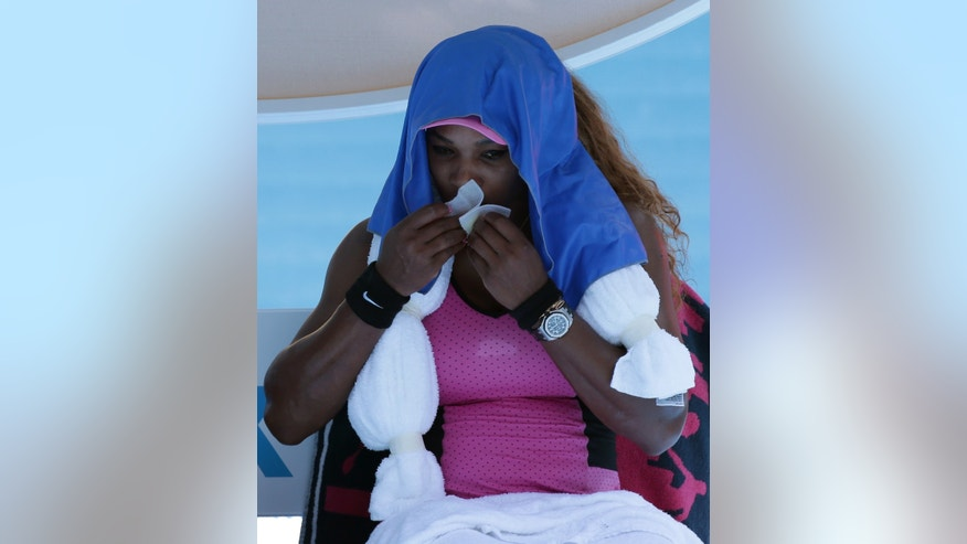 Serena Williams of the U.S. cools down with ice towel on her shoulders between games during her third round match against Daniela Hantuchova of Slovakia at the Australian Open tennis championship in Melbourne, Australia, Friday, Jan. 17, 2014. (AP Photo/Aaron Favila)