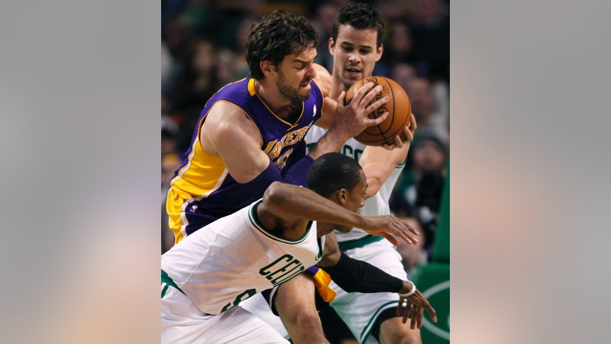 Boston Celtics guard Rajon Rondo, front, tries to knock the ball free from the hands of Los Angeles Lakers center Pau Gasol, top left, during the first quarter of an NBA basketball game in Boston, Friday, Jan. 17, 2014. Celtics forward Kris Humphries looks on. (AP Photo/Charles Krupa)